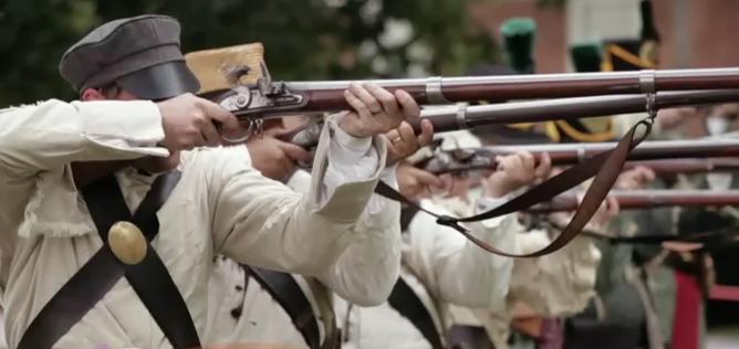 Reenactors of Worthington pioneers shooting muskets.