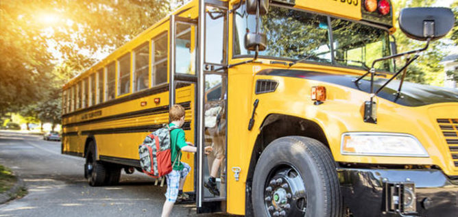 student getting on a school bus
