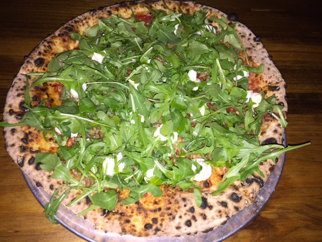 The Ricky Ricotta pizza at Paulie Gee's features sweet Italian fennel sausage, pecorino Romano, extra virgin olive oil, arugula, and post-oven ricotta.