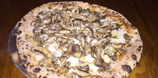 "The ""Some Guys Have All the Fun"" pizza at Paulie Gee's with mushroom duxelles, extreme mushroom mix, thyme, mozzarella, fontina, and truffle oil."