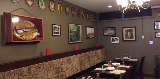 The dining areas at Valter's at the Maennerchorare are warm and feature German banners.