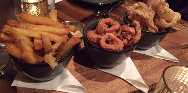 The triple cooks fries (from left), cayenne pickled onion rings with whole grain honey mustard and pork rinds with espresso are some of the many sharable sides at Rockmill Tavern. Photo: Steve Stover
