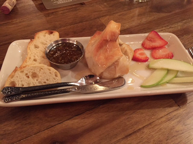 Baked French brie in a phyllo shell with orange marmalade, apples, and strawberries at Napa Kitchen + Bar.
