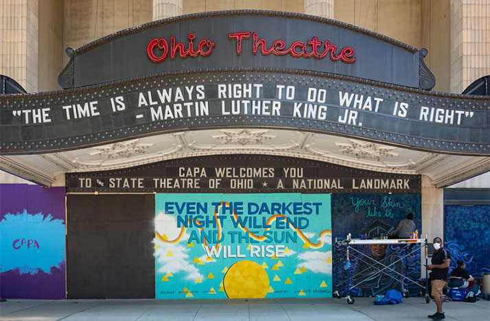 A group of artists were paid to paint temporary murals over the boarded-up windows of the Ohio Theatre on June 2, 2020, after it was damaged during protests. RYAN HITCHCOCK / WOSU