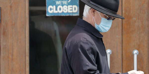 A man walks past a closed business Wednesday, April 29, 2020, in Shaker Heights, Ohio. TONY DEJAK / ASSOCIATED PRESS