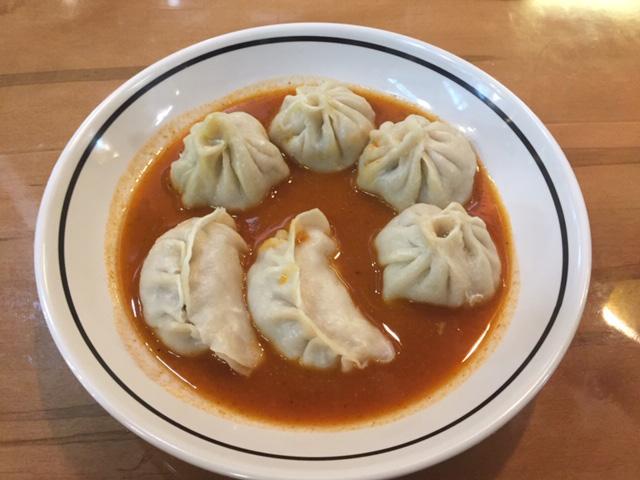 Momo Ghar dumplings served in a tomato-based sauce. Photo: Steve Stover