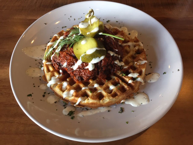 Nashville hot chicken on a savory ham and herb waffle, with dill buttermilk sauce and house-made horseradish pickles at Alqueria Farmhouse Kitchen. Photo: Steve Stover