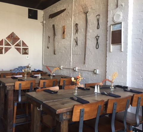 The interior at Alqueria Farmhouse Kitchen features reclaimed wood and agriculture tools. Photo: Steve Stover