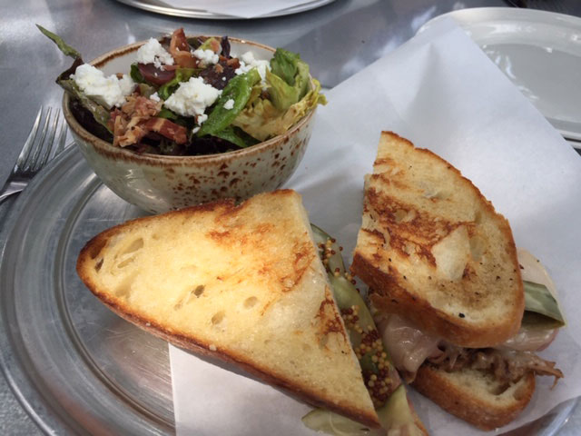 The Cuban-OH sandwich at the Old Spot features braised Ohio pork, house ham, pickles, Swiss, and aioli on homemade pagnotta, an Italian-style country round loaf of bread.