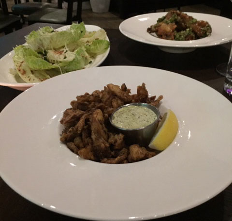 Caesar salad (left), crispy mushrooms (center), and chicken wings (right) at See Saw restaurant in the Short North Photo: Steve Stover