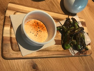Charred Shishito peppers accompanied with  a highly spiced sriracha aioli and smoked sea salt at Sow Plated. Photo: Rich Terapak.