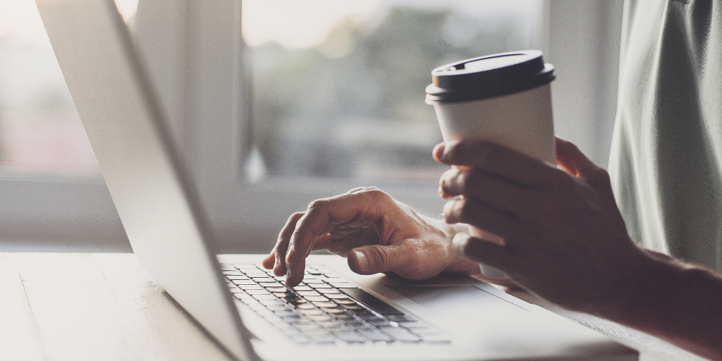 A person typing on a laptop with one hand while holding a cup of coffee in their other hand.