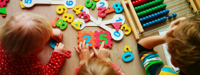 Image of young children playing with number blocks and other learning toys