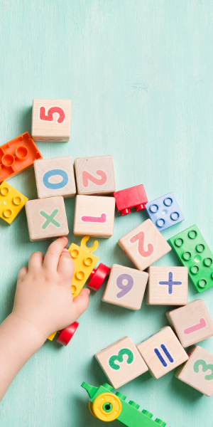 A small childs hand reaching for wooden blocks with numbers printed on them in bright colors.
