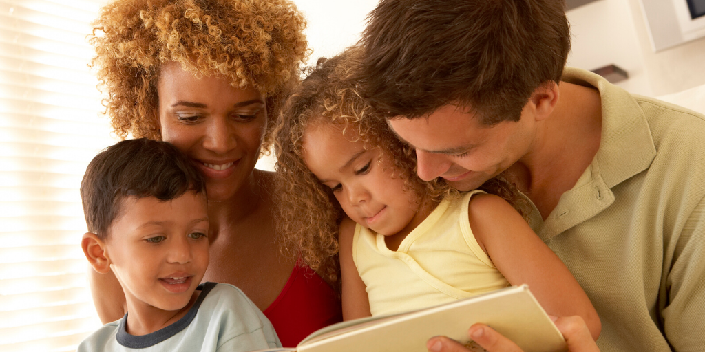 A mother and father reading a book to their two young children