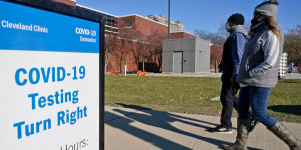 Two people walk past a sign for COVID-19 testing at the Cleveland Clinic, Wednesday, Nov. 18, 2020, in Cleveland. TONY DEJAK / ASSOCIATED PRESS