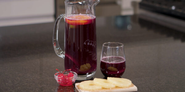 Sing-to-Me-Sangria - a pitcher of sangria, a glass, and garnishes