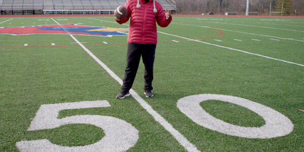 Dr. Fredric Bertley host of QED with Dr B on a football field