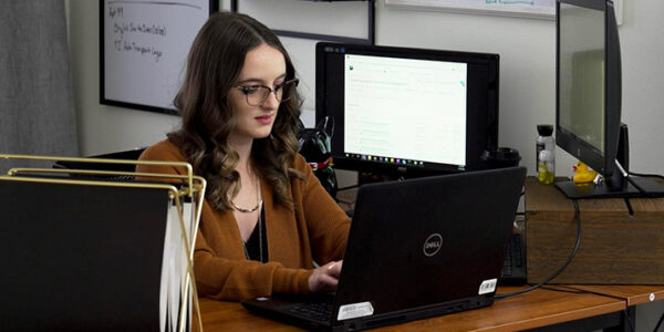 Software engineer Kait Matthey does work on her laptop computer