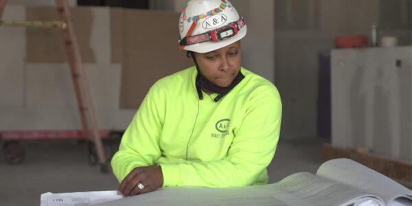 Rebecca Lewis reviews blueprints at a construction site.